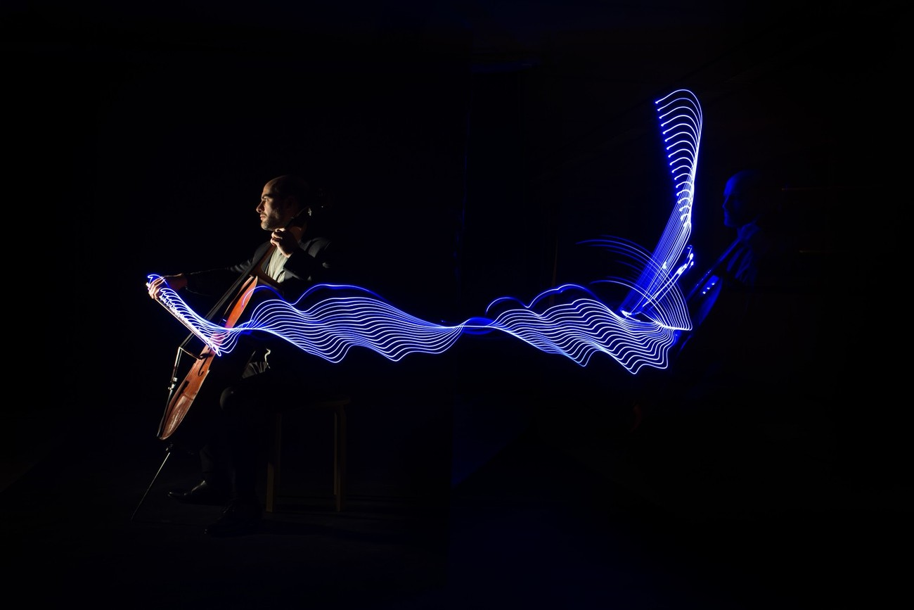 Long exposure light painting with an LED strip taped to the bow.  The portrait on the right is lit by the LED only, with the camera immobile. When the cellist started playing, the camera was panned to the right. A studio flash was fired on the second curtain.  Cellist: Antonis Pratsinakis www.antonispratsinakis.com  20171207 170