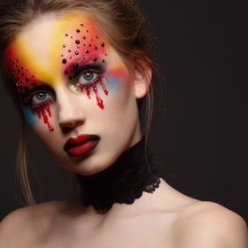 Portrait of young and beauty female model with creative makeup, bloody eyes and black rhinestones