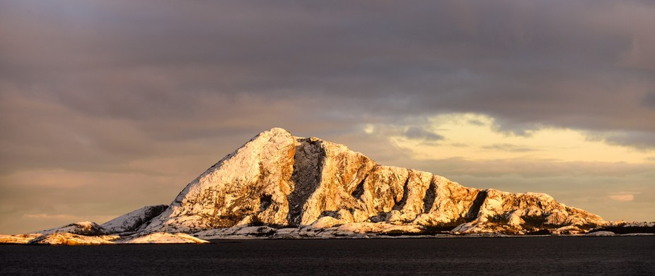 This mountain catches the some rays of early morning light with a contrasty black sky near Ørnes