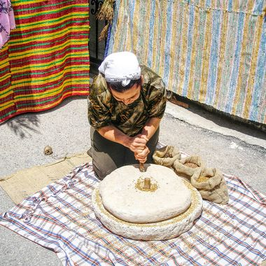This photo was taken at the Büyükkonuk Eco Festival, in the year 2011. The woman from the village was demonstrating how the villagers used to grind wheat between two flat stones.