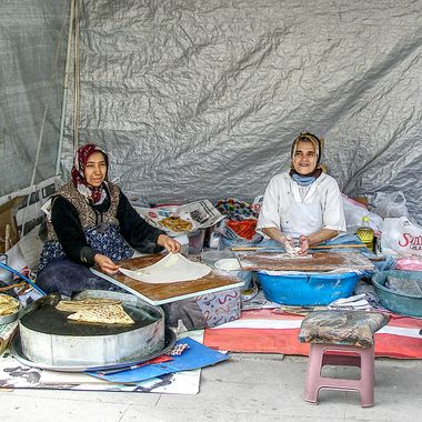 I took this photo when me and my wife went to Eskisehir, Turkey in the year 2011. As we were walking around the market, I saw these women preparing traditional food. So, this was one of the photos I took that day.