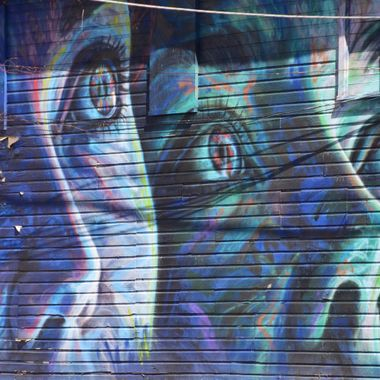 City mural on side of dilapidated building. Faces and eyes in shades of green, blue and violet