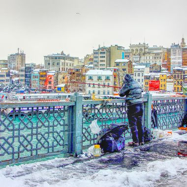 I took this photo when my wife and I were in Istanbul, in the year 2015. We were walking in the snow on the Galata bridge and when I saw these fishermen I decided to take this photo.