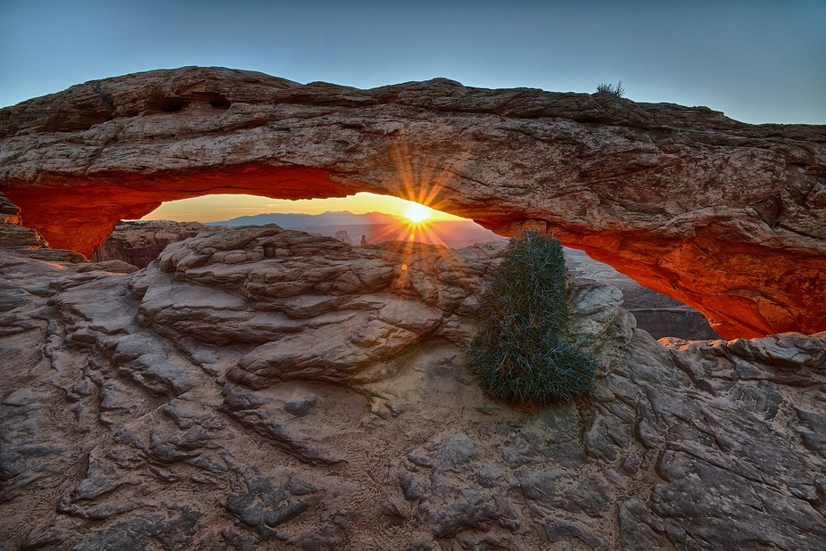 The sun rises over the La Sal Mountains through Mesa Arch, Island in the Sky District, Canyonland...