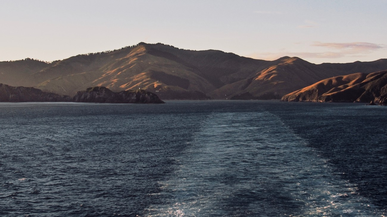 From the rear deck of a ferry, the rolling hills sit behind in the early evening sun