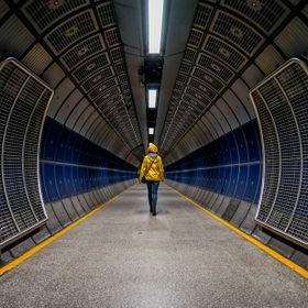 A woman walks through a tube station in London, UK