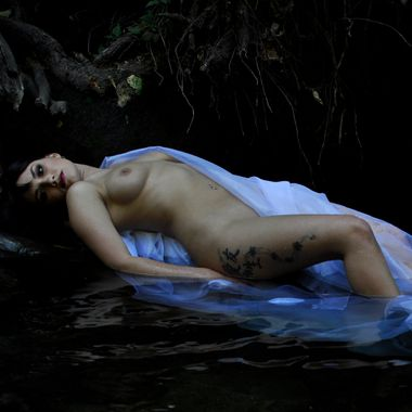 A sexy brunette woman reclines in mysterious dark water below gnarly roots deep in the forest.