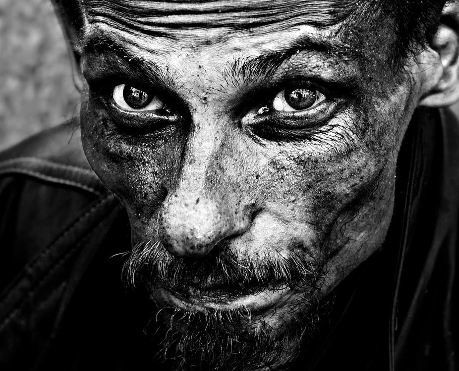 Black-and-white portrait of a homeless man, taken in Prague street.