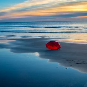 Abandoned red umbrella on the beach of Litchfield South Carolina USA.
