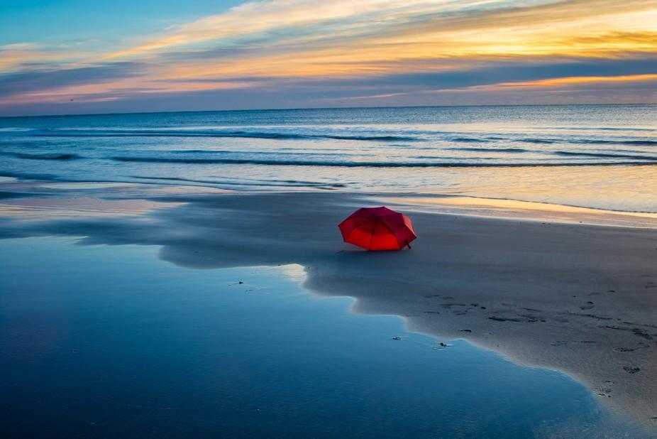 Abandoned red umbrella on the beach of Litchfield South Carolina USA.