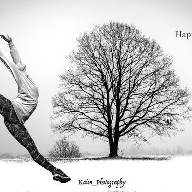 Ballet dancer jumping around a tree in the winter