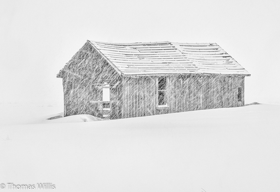 Abandoned cabin in a snow storm.