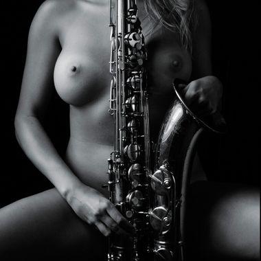 A nude woman masturbates metaphorically with a saxophone.