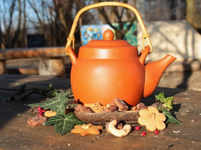 Orange teapot with Christmas cakes and ivy leaves