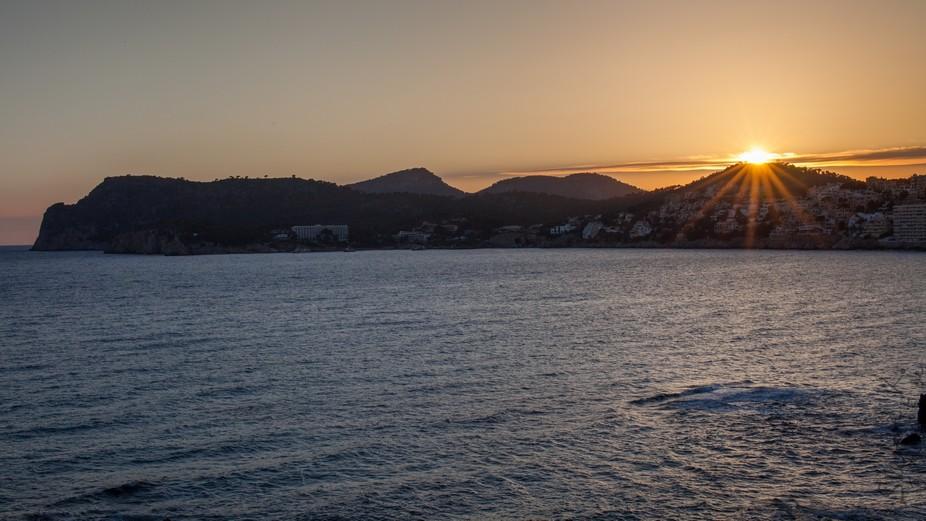 Last sunbeams before sunset at Pagueras Beach, Mallorca, Spain