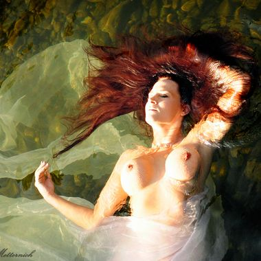 A red headed mermaid floats in icy waters during the heat of summer.