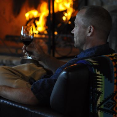 A man sips red wine by the fire on a winter day