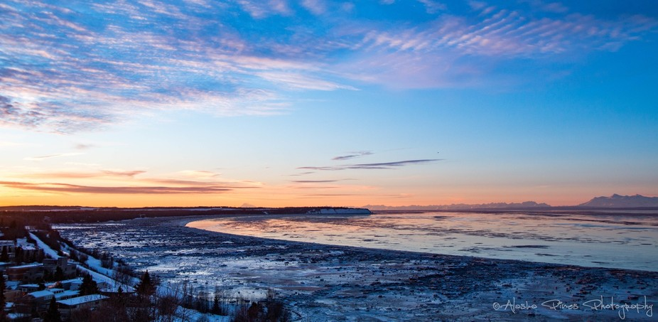 A beautiful sunset overlooking the Knik arm of Cook Inlet, from a rooftop in downtown Anchorage, where you can see the active Redoubt Volcano. The tides around Alaska rise and fall twice a day, and what's shown here is a low tide. This affects when the cargo ships and cruise liners can dock in any of our ports. You can see all the ice chunks left behind when the water receded.