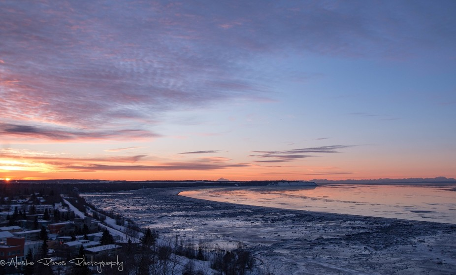A beautiful sunset overlooking the Knik arm of Cook Inlet, from a rooftop in down-town Anchorage, where you can see the active Redoubt Volcano. The tides around Alaska rise and fall twice a day, and what's shown here is a low tide. This affects when the cargo ships and cruise liners can dock in any of our ports. You can see all the ice chunks left behind when the water receded.