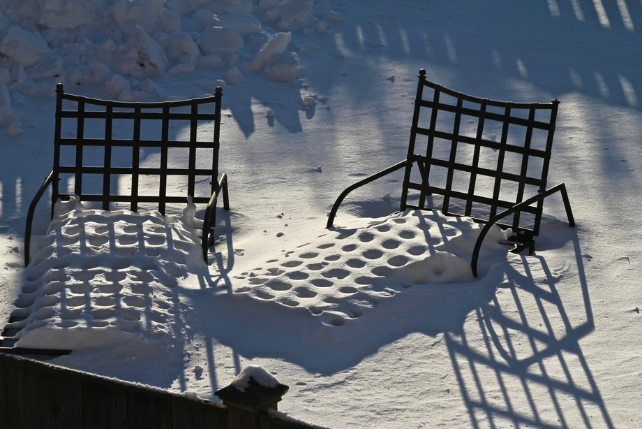 Wrought-iron lounge chairs in the snow; the shadows from the late afternoon sun were distinctive ...