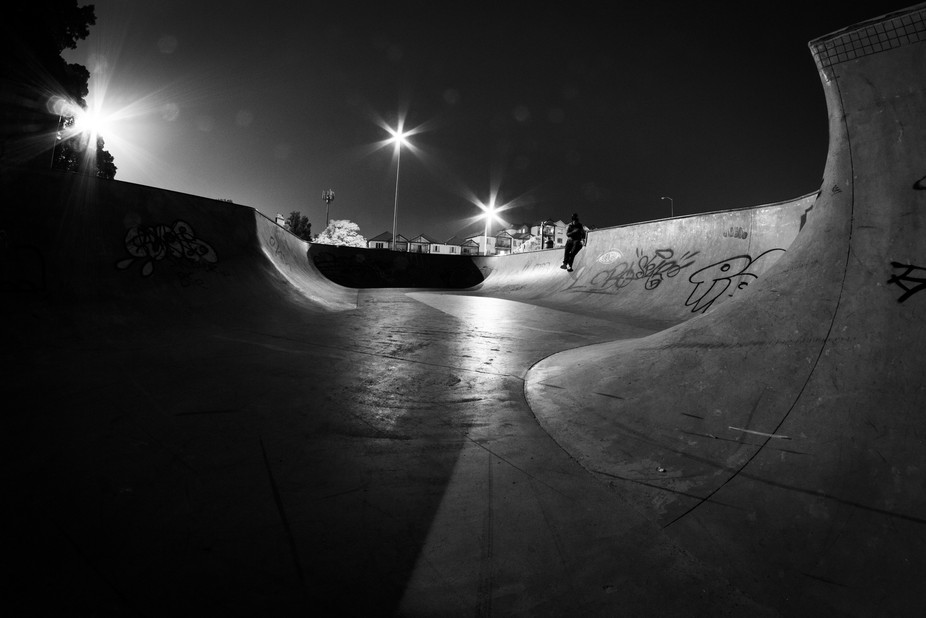 Night shot of the local skate park with a sole person chilling