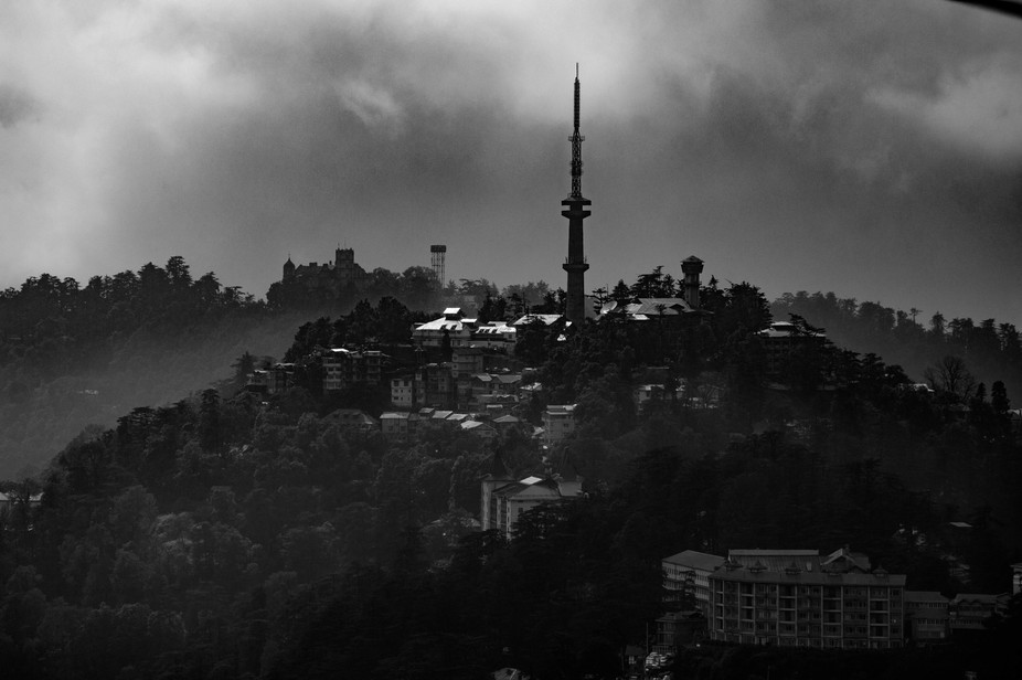 The city tower of Mcleodganj in Himachal Pradesh, India, surrounded by dense foggy clouds