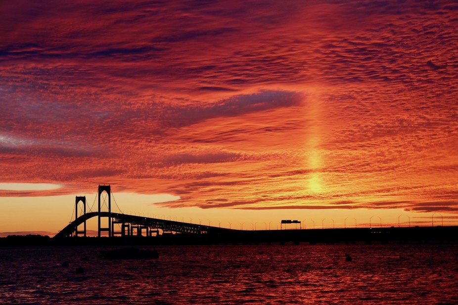 A more rare sunset to the West of the Newport Bridge.  The glow from the sun appeared for just mo...