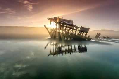 A shipwreck at sunrise on the beach.