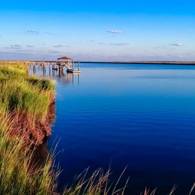 Dock on Daufuskie Island in Beaufort South Carolina surrounded by marsh and deep blue waters from the intercoastal waterway.