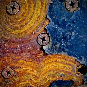 The rust and peeling paint on a hinge resemble the sun, the beach and the sky.