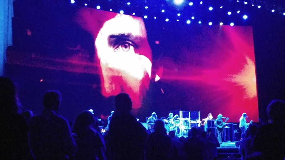 Screen depiction of animated eerie colorful photo of Pete Townsend while band playing live below.