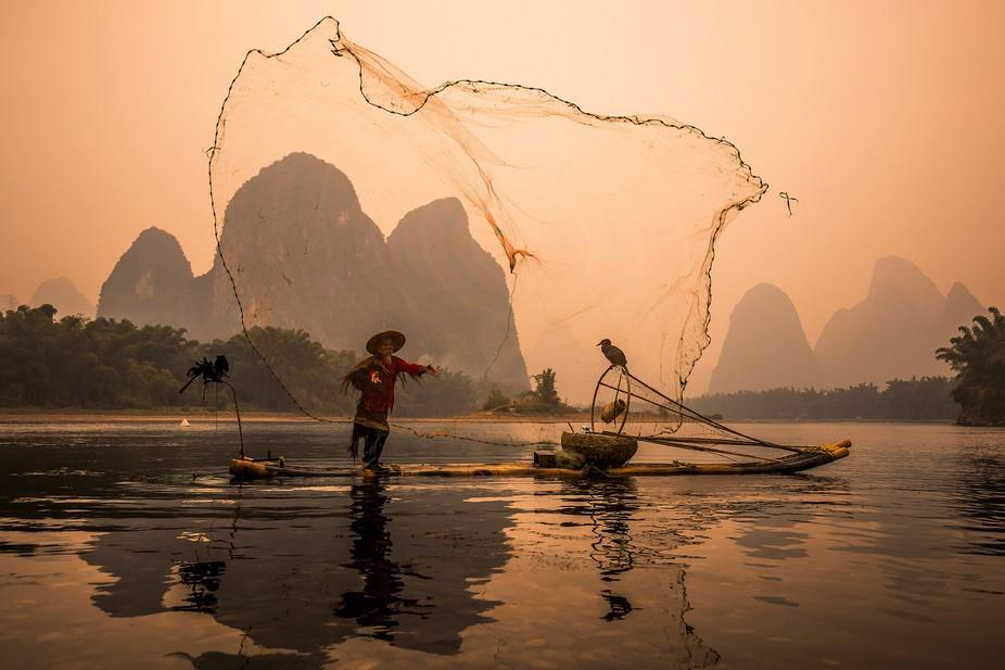 Cormorant Fisherman throwing fishing net on a Li River, China.