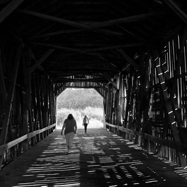 Two people walking through an old covered bridge.