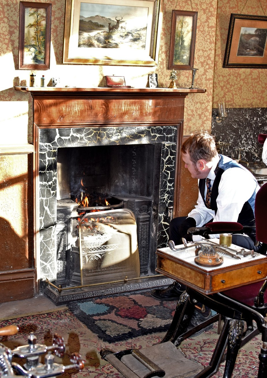 Dentist at Beamish museum keeping warm on a winters day,