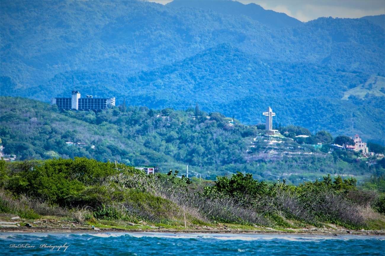 """From Wikipedia, the free encyclopedia:  Cruceta del Vigía (English: The Watchman Cross) is a 100 feet (30 m) tall cross located atop Vigia Hill in Ponce, Puerto Rico, across from Museo Castillo Serrallés. It houses a tourist center at its base, a ten-story vertical tower, and a horizontal sky bridge that has panoramic views of the city of Ponce and the Caribbean Sea. Visitors can reach the skybridge via glass elevators or a staircase. Made of reinforced concrete, the cross has withstood various natural disasters, including three major hurricanes. The arms of the cross measure 70 feet. It was inaugurated in 1984.[3]  One of many landmarks of the city of Ponce, the cross is owned by the Municipality of Ponce and is currently operated by the """"Patronato de Ponce"""", a non-profit organization dedicated to preserving and administrating several of the city's landmarks.  Historical background[edit]  View of El Vigia Cross. The cross sits at the same spot on Vigia Hill where early Spanish settlers once looked out for merchant ships and would-be invaders, including marauding pirates. In 1801, the settlers built a much smaller cross made of two intersecting tree trunks where an observer would constantly watch the sea and the city's port, raising different flags to either notify local merchants of incoming trade ships or alert military authorities of possible threats (a replica of this wooden cross now sits behind the current monument). Originally a hut was built accompanied by a cross from where flags were raised to signal the approach of ships as well as their port of origin. This station was run by two brothers Ricardo and Alberto Lugo, they were honored with a plaque at the base of the cross in 1984. They are descendants of Alonso Fernández de Lugo last conquistador of Spain.[4]  One of the best remembered watchmen was named Luis Castro. Nearly 200 years ago, Luis would sit atop a huge wooden cross on this hill. On the lookout for ocean vessels, it was his responsibility to d"""
