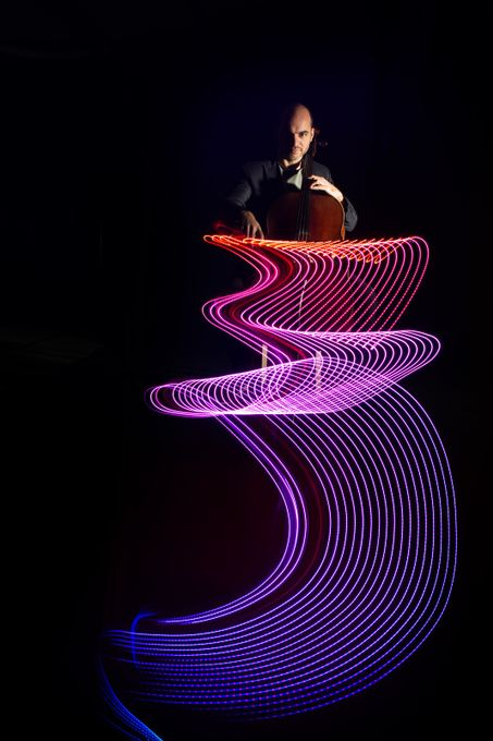 Photo session with cellist Antonis Pratsinakis in the studio. An LED strip with changing colours was taped to the bow. While the cellist played in the dark, the camera was moved vertically, thereby visualising his music. A flash was fired at the end of the exposure.  Inspired by Stephen Orlando. 20171207 128