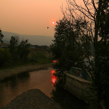 Coldwater River runs through Merritt and is reflecting the red sun. The Smoke from the forest fires is hanging thick in the valley.