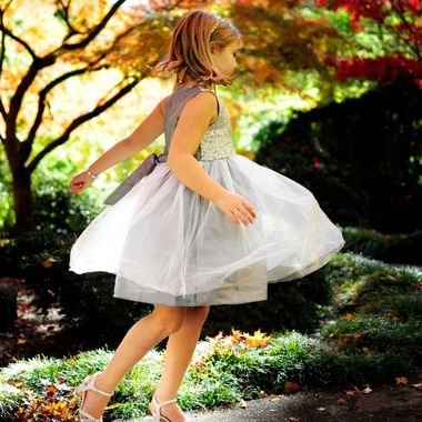 A girl in a beautiful dress dances in the Japanese Gardens with brilliant Autumn leaves.