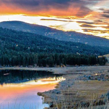 The sun setting and reflecting in Garcia Lake near Merritt B C
