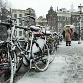Snowy day in amsterdam. The bikes parked under the snowfall.