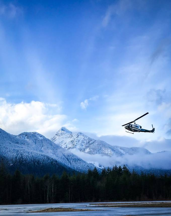 Break in rain and snow just before the sunset. Clouds parted revealing beautiful snow covered mountains with this Helicopter doing training at Squamish Airport.