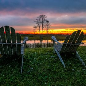 retirement and two chairs looking at the sunset in the swamp
