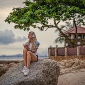Beautiful blonde woman sitting on a rock by the sea and listening to music with your tablet. hands with tattoos. Style summer vacation. Modern girl