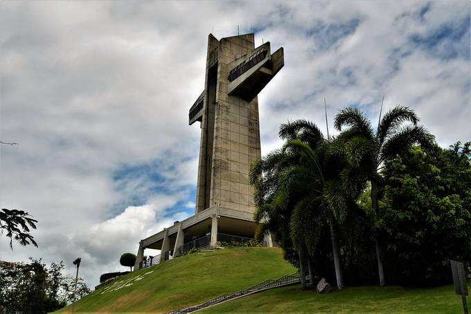 """From Wikipedia, the free encyclopedia:  Cruceta del Vigía (English: The Watchman Cross) is a 100-foot-tall cross located atop Vigia Hill in Ponce, Puerto Rico, across from Museo Castillo Serrallés. It houses a tourist center at its base, a ten-story vertical tower, and a horizontal sky bridge that has panoramic views of the city of Ponce and the Caribbean Sea. Visitors can reach the skybridge via glass elevators or a staircase. Made of reinforced concrete, the cross has withstood various natural disasters, including three major hurricanes. The arms of the cross measure 70 feet. It was inaugurated in 1984.[3] One of many landmarks of the city of Ponce, the cross is owned by the Municipality of Ponce and is currently operated by the """"Patronato de Ponce"""", a non-profit organization dedicated to preserving and administrating several of the city's landmarks.  Historical background[edit]  View of El Vigia Cross. The cross sits at the same spot on Vigia Hill where early Spanish settlers once looked out for merchant ships and would-be invaders, including marauding pirates. In 1801, the settlers built a much smaller cross made of two intersecting tree trunks where an observer would constantly watch the sea and the city's port, raising different flags to either notify local merchants of incoming trade ships or alert military authorities of possible threats (a replica of this wooden cross now sits behind the current monument). Originally a hut was built accompanied by a cross from where flags were raised to signal the approach of ships as well as their port of origin. This station was run by two brothers Ricardo and Alberto Lugo, they were honored with a plaque at the base of the cross in 1984. They are descendants of Alonso Fernández de Lugo last conquistador of Spain.[4] One of the best remembered watchmen was named Luis Castro. Nearly 200 years ago, Luis would sit atop a huge wooden cross on this hill. On the lookout for ocean vessels, it was his responsibility to determine """