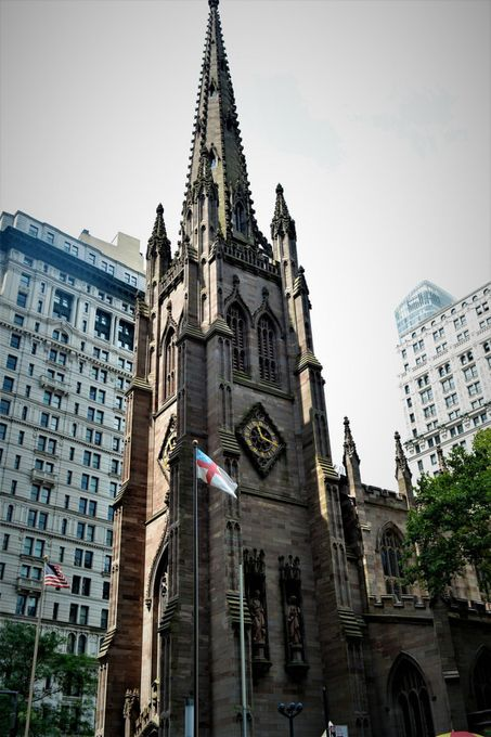 """From Wikipedia, the free encyclopedia:  Trinity Church is an historic, active, well-endowed[4] parish church in the Episcopal Diocese of New York. It is located near the intersection of Wall Street and Broadway, in the lower Manhattan section of New York City, New York. Trinity, a traditional High church, is a very active parish around Episcopal Church and the worldwide Anglican Communion in missionary, outreach, and fellowship.  History and architecture[edit] The Trinity Church has been significant to New York City's history for over 300 years. In 1696, Governor Benjamin Fletcher approved the purchase of land in Lower Manhattan by the Church of England community for construction of a new church. The parish received its charter from King William III on May 6, 1697. Its land grant specified an annual rent of 60 bushels of wheat.[5] The first rector was William Vesey (for whom nearby Vesey Street is named), a protege of Increase Mather, who served for 49 years until his death in 1746 First Trinity Church[edit]  Loyalist Charles Inglis, Rector of Trinity Church (1765-1783) The first Trinity Church building, a modest rectangular structure with a gambrel roof and small porch, was constructed in 1698, on Wall Street, facing the Hudson River. The land on which it was built was formerly a formal garden and then a burial ground.[6][better source needed][7][8][9] It was built because in 1696, members of the Church of England (Anglicans) protested to obtain a """"charter granting the church legal status"""" in New York City. According to historical records, Captain William Kidd lent the runner and tackle from his ship for hoisting the stones.[10][11] Anne, Queen of Great Britain, increased the parish's land holdings to 215 acres (870,000 m2) in 1705. Later, in 1709, William Huddleston founded Trinity School as the Charity School of the church, and classes were originally held in the steeple of the church. In 1754, King's College (now Columbia University) was chartered by King George"""