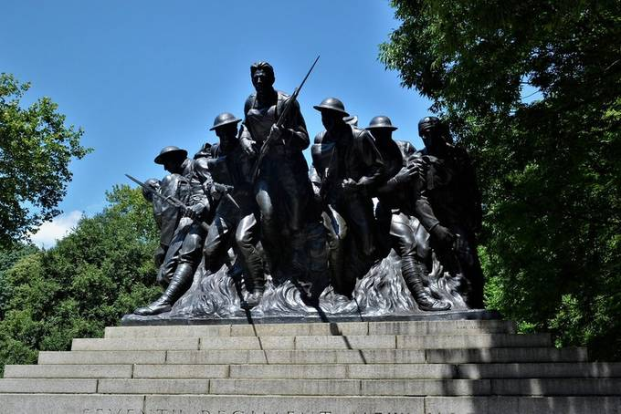 """107th Infantry Memorial  From Wikipedia, the free encyclopedia:  107th Infantry Memorial is an outdoor bronze sculpture and memorial by sculptor Karl Illava. The base sits upon a 25-foot wide stepped granite; designed by architects Rogers and Haneman. It is located at the intersection of East 67th Street at Fifth Avenue in Central Park, in Manhattan, New York. It depects a group of seven men with various roles during the fighting in World War I. It was donated by the Seventh Regiment New York 107th United States Infantry Memorial Committee. [1] C.I. De Bevoice was the head of the fund raising for the Memorial Committee. He was the Colonel in charge of the 107th Infantry in 1917.[2]  Inscription[edit] There is an inscription on the monument. It states """"SEVENTH REGIMENT NEW YORK / ONE HUNDRED AND SEVENTH UNITED INFANTRY / 1917 IN MEMORIAM 1918"""".(Inscription all in capitol letters) Dedication[edit]  The memorial at night Over 5,000 people [3] attended the dedication of the monument on September 29, 1927, on the 9th anniversary of the Battle of St. Quentin Canal, an attack on the Hindenburg Line.[4] Speakers included Colonel Hanford MacNider, the Assistant Secretary of War, New York State Senator William T. Byrne, Major General John F. O'Ryan, and General Alexander S. Diven.[4] The presentation address was by Lieutenant Colonel Nicholas Engel of the 107th.[4] The sons of two fallen members of the 107th, Captain Clinton E. Fisk of Company D and Captain Fancher Nicoll of Company L., unveiled the monument.[4] When it was unveiled, many people speculated that the lead soldier was modeled after boxer Gene Tunney, but """"[o]fficers of the regiment denied this, saying the sculptor merely had striven to emphasize the characteristic expression of the typical soldier in action""""[3] and the sculptor said the figure was based on advertising executive Paul Cornell.[5] Remembrance Ceremonies[edit] On Armistice Day 1927. the 107th Infantry Post of the American Legion held a religious ser"""