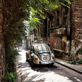 Old city with old abandoned houses and this is a magical moment with old car passing by. the old house is abandoned but there is life around .. n...