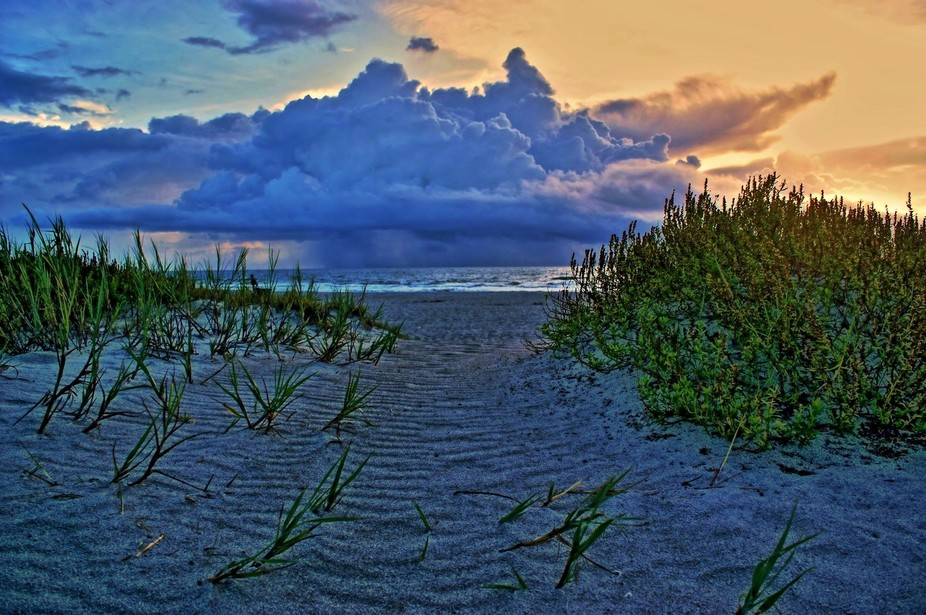 The sunrise reveals an offshore thunderstorm along the sands of Cocoa Beach, Florida