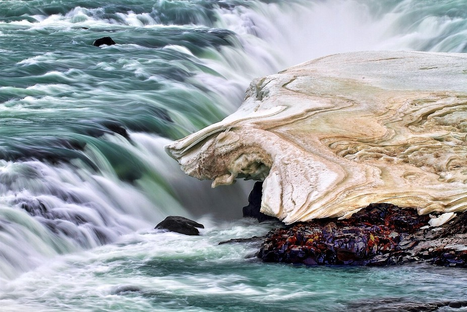 Water rushing under the the melting snow along a running river in Iceland makes for a colorful ba...