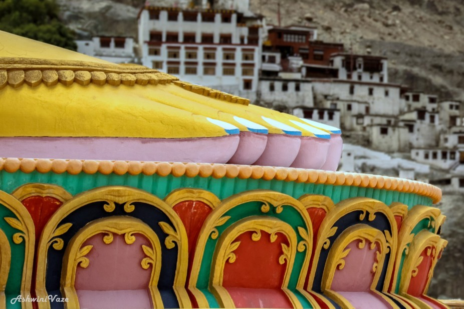 Lotus feet of the statue of Buddha at Diskit Monastery. In the background, houses of Diskit, Lada...